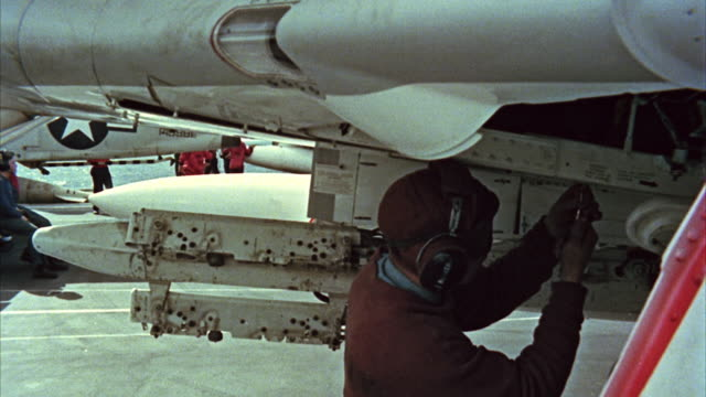 vídeos de stock e filmes b-roll de montage ground crew preparing fighter on aircraft carrier - protetor de ouvido