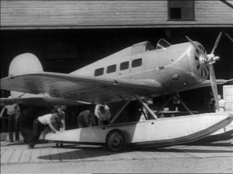 ground crew pushing wiley post's orion-sirius hydroplane out of hangar / documentary - 1935 stock videos & royalty-free footage