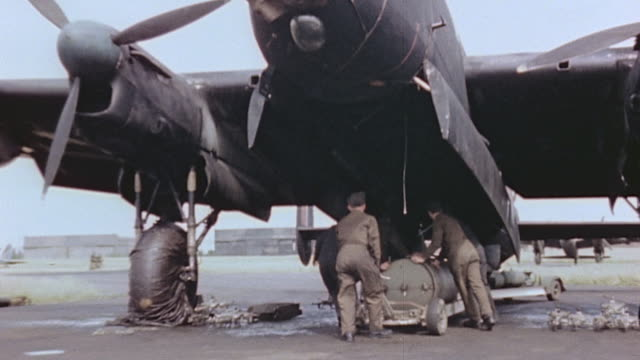 ground crew rolling blockbuster bombs on trailer beneath parked lancaster for loading as tractor drives past towing more blockbusters on trailer - beladen stock-videos und b-roll-filmmaterial