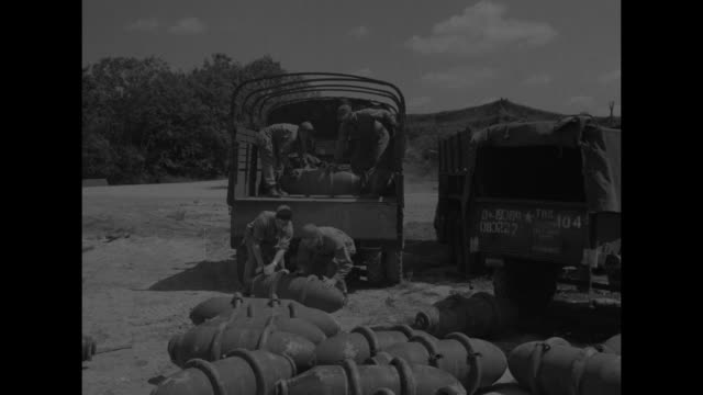ground crew rolls bombs on bomb trolley toward b-17 bomber waiting on tarmac / vs ground crews unload bombs from back of trucks, roll on ground / mls... - waist stock videos & royalty-free footage