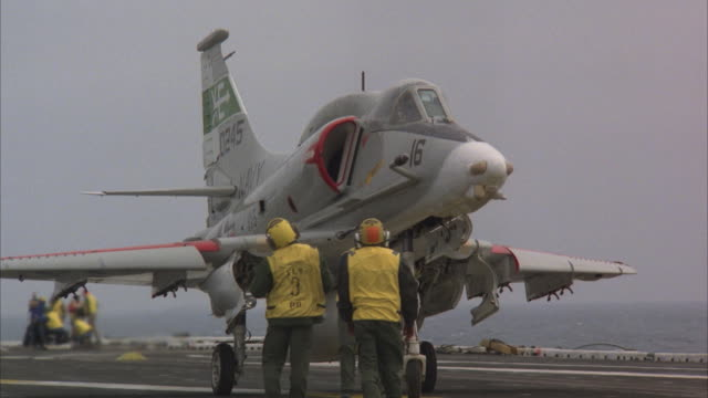 MS, PAN, Ground crew towing skyhawk military jet on aircraft carrier