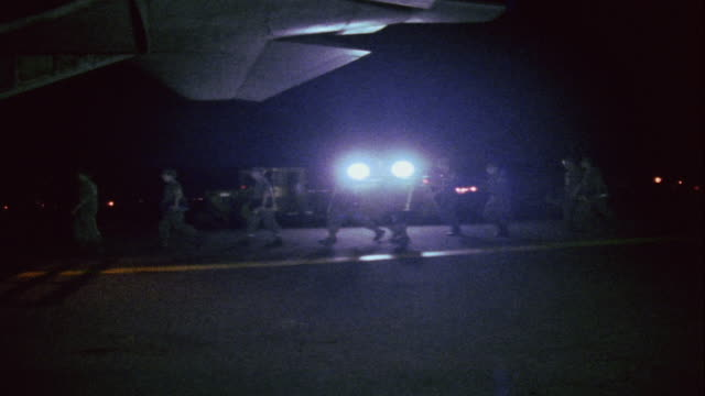 ws ground crew walking past vehicle headlights on nighttime base / da nang vietnam - ダナン点の映像素材/bロール