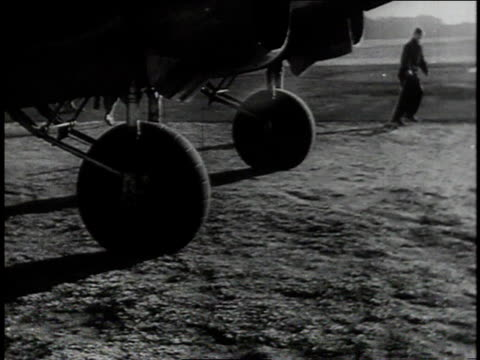 vidéos et rushes de ground crewman yanking chock from wheel / bomber taxiing / nose cone and propellers against the sky / - world war 1
