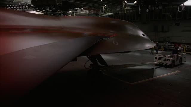 ground crews work on fa18 hornets in a hanger. - hangar stock-videos und b-roll-filmmaterial