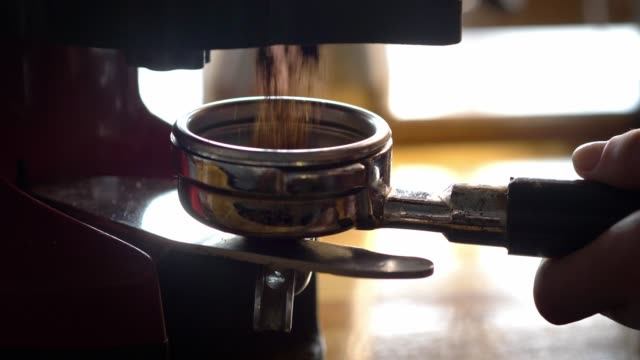 ground espresso being measured into a portafilter at an espresso shop. - espresso maker stock videos and b-roll footage