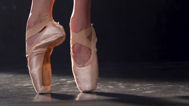 ground level shot of a classical ballet dancer, dancing on a black stage, with view of her feet and pointe shoes - anmut stock-videos und b-roll-filmmaterial