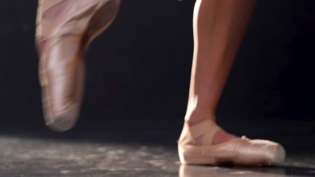 ground level shot of a classical ballet dancer, dancing on a black stage, with view of her feet and pointe shoes - accuracy stock videos & royalty-free footage