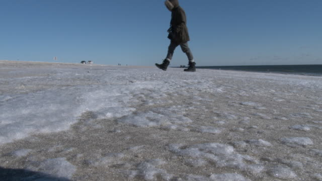Ground level shot of ice covering the sand on Jones Beach New York as an arctic outbreak brings bitter cold temperatures to the area