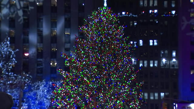 ground level shot of the rockefeller plaza christmas tree lighting - christmas tree lighting ceremony stock videos & royalty-free footage