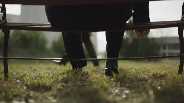 stockvideo's en b-roll-footage met ground level shot reenactment of a man sitting on a bench and hiding a small object under the seat during the 1980s - spion