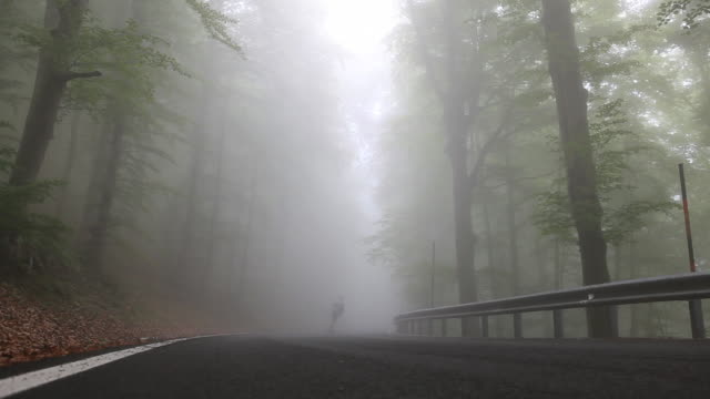 ground level view of longboarder descending foggy road - one teenage boy only stock videos & royalty-free footage
