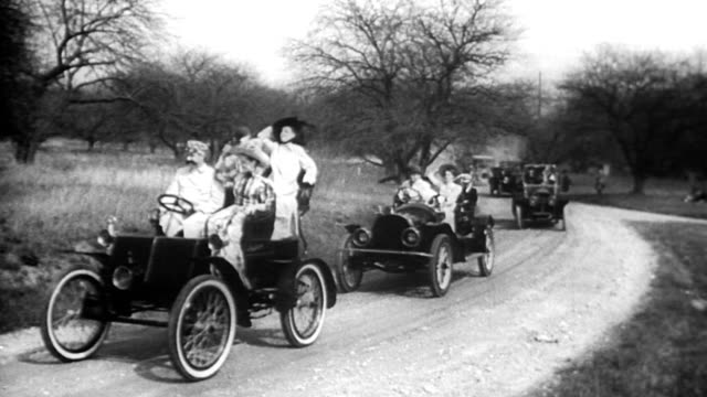 vídeos de stock, filmes e b-roll de ground level views of 1940s cars on highway, cars bumper-to-bumper in highway traffic jam / parade of antique cars in 'golden jubilee 1896-1946'... - 1946