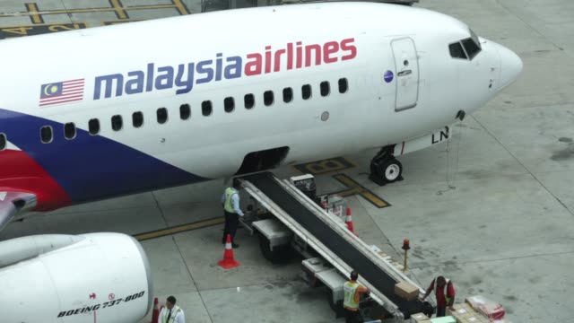 stockvideo's en b-roll-footage met ground staff load an aircraft operated by malaysian airlines system bhd at kuala lumpur international airport in sepang, malaysia, on friday, aug 8... - petronas twin towers