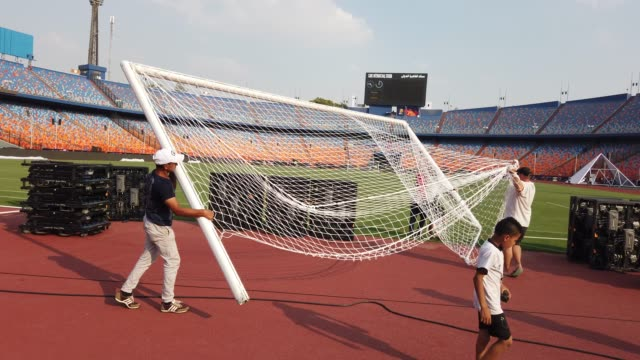 vidéos et rushes de ground staff move the goal into place during preparations for african cup of nations at the cairo international stadium on june 17th 2019 in cairo... - cage