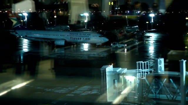 ground staff refuelling plane through wing cape town international airport is located in cape town south africa and is the third busiest airport in... - 給油点の映像素材/bロール