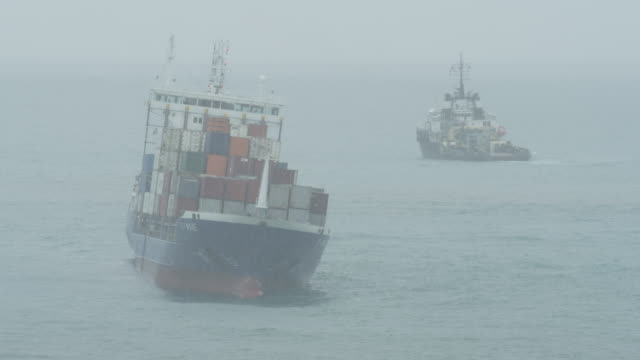 LS grounded container ship and tug during storm