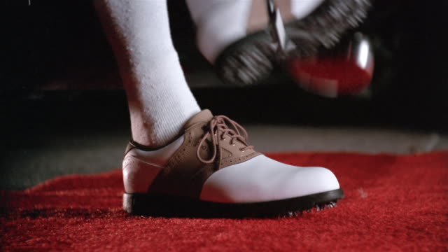 ground-level view of red carpet / feet of man in golf cleats stepping out of limo with club and walking down carpet as camera flashes go off - golf shoe stock videos & royalty-free footage