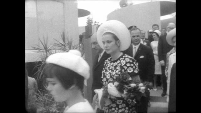 grounds of expo 67 in montreal / prince rainier and princess grace walking around on monaco national day / visit with people and drink champagne /... - monaco stock-videos und b-roll-filmmaterial