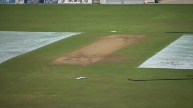 groundsheets cover a part of the field at the oval cricket ground. available in hd. - pitch stock videos & royalty-free footage