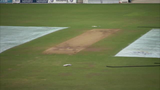 vidéos et rushes de groundsheets cover a part of the field at the oval cricket ground. available in hd. - terrain de sport sur gazon
