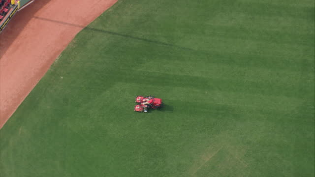 aerial groundskeeper riding a lawnmower cutting grass in the field of fenway park baseball stadium / boston, massachusetts - lawn mower stock videos and b-roll footage