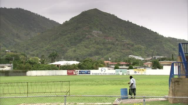 vídeos de stock e filmes b-roll de a groundskeeper uses a hose at st. mary's college cricket ground. available in hd. - índias ocidentais