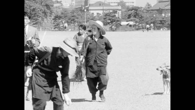 groundskeepers pick litter around tourists in tokyo; 1964 - グランドキーパー点の映像素材/bロール