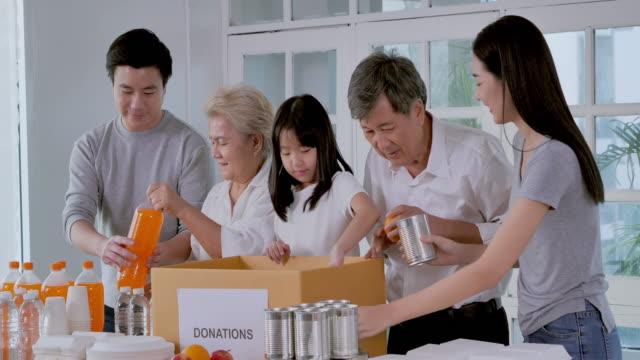 grupp asiatiska familj av volontärer för packning mat och dryck donationer för hemlösa under. undervisning/lärande om donationskoncept.sydostasien och östasien: personer i åldern 50+ - east asian ethnicity bildbanksvideor och videomaterial från bakom kulisserna