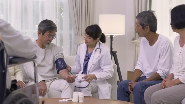 アジアの若い女性看護師医師が血圧測定のチェックと老人ホームでの医療相談を説明する60-70歳のグループアジアの高齢者。ホームヘルスケアのコンセプト。 - 訪問点の映像素材/bロール
