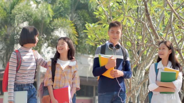 stockvideo's en b-roll-footage met de aziatische tiener die van de groep samen actief en gelukkig naar school gaat. onderwijs, terug naar school, mensen, lifestyle, vriendschap concept. - chinese etniciteit