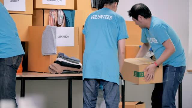 vídeos y material grabado en eventos de stock de grupo asiático joven adulto de voluntario preparando entrega gratuita de alimentos y ropa para las personas de crisis coronavirus covid-19. voluntariado - sin techo