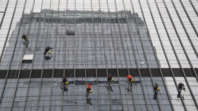 A group cleaner washing windows at a high building