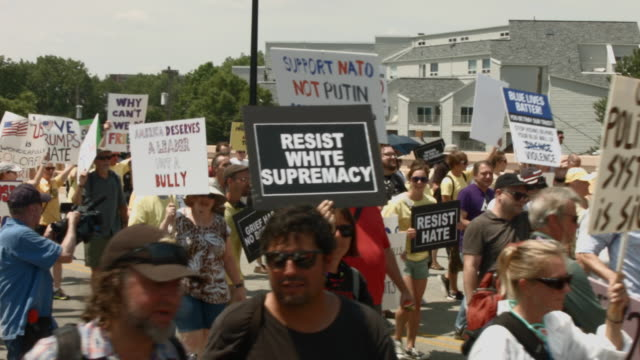a group demonstrating against republican presidential candidate donald trump march near the site of the republican national convention on the last... - republikanischer parteitag stock-videos und b-roll-filmmaterial