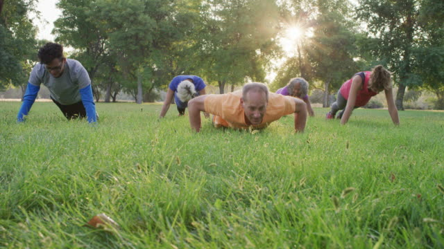group doing pushups in park - exercise class stock videos & royalty-free footage