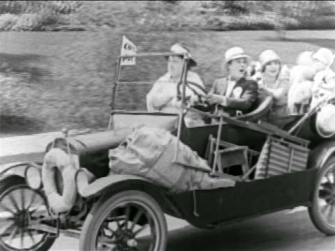 B/W 1927 group driving in convertible waving to someone off screen / feature