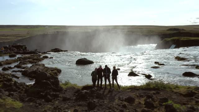 vidéos et rushes de selfie de drone de groupe à la chute d'eau de godafoss en islande - paysage enchanteur