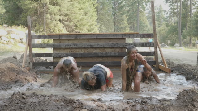 group emerging from mud pit during adventure race - heroes stock videos & royalty-free footage