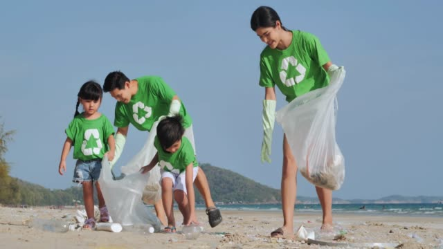 vídeos de stock e filmes b-roll de group family of happy volunteers with garbage bags cleaning area on the beach.volunteering, charity, people and ecology concept.volunteerism - lixo