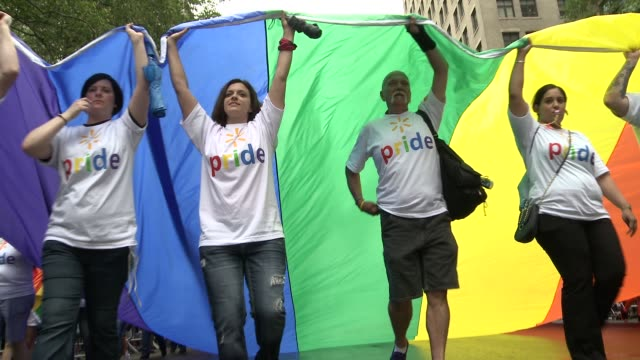group from wall mart wearing pride t-shits carry a giant rainbow flag down the parade route / the giant flag passes over and engulfs the camera in... - t shirt stock videos & royalty-free footage