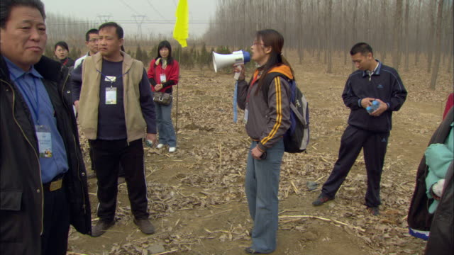 MS PAN Group gathered around woman speaking into bullhorn at tree planting ceremony / Beijing, China