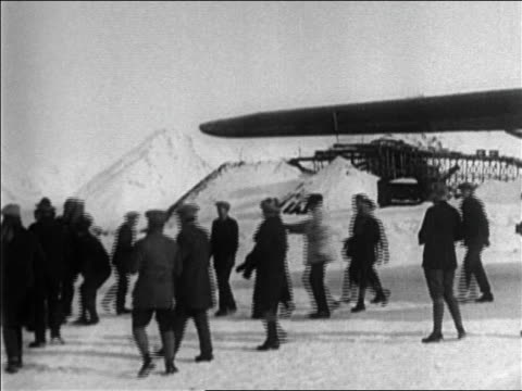 vidéos et rushes de pan group gathered under wing of airplane on arctic tundra - 1926