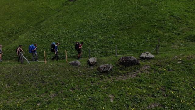 vidéos et rushes de groupe de randonnées le long de la clôture de fil barbelé dans les alpes - 50 54 ans