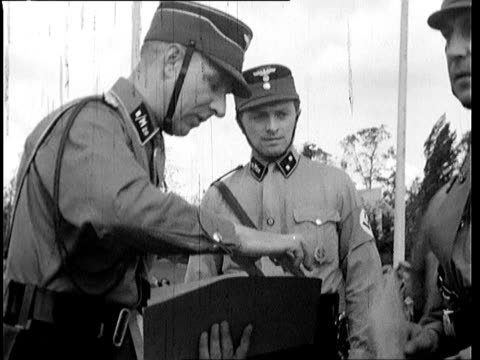 group leaders hand out some kind of certificate to soldiers talk among higher ranked officers inspection highest ranking officer given nazi salute - 将校点の映像素材/bロール