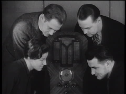 b/w 1939 group of 3 men woman sitting around radio with ears pressed to speakers / newsreel - radio stock videos & royalty-free footage