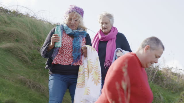 A group of 3 women swimmers walking down a rocky coastal path on their way to the beach.