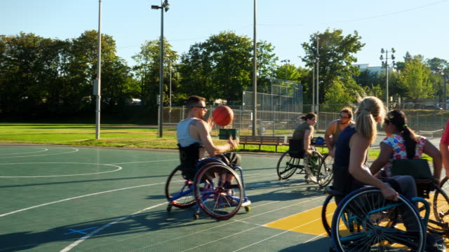 vidéos et rushes de ms group of adaptive athletes playing basketball game on outdoor basketball court on summer evening - chaise roulante