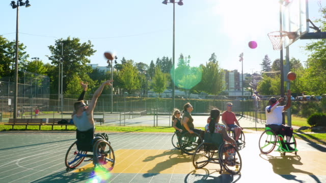 ms group of adaptive athletes warming up before basketball practice on outdoor court - wheelchair basketball stock videos and b-roll footage