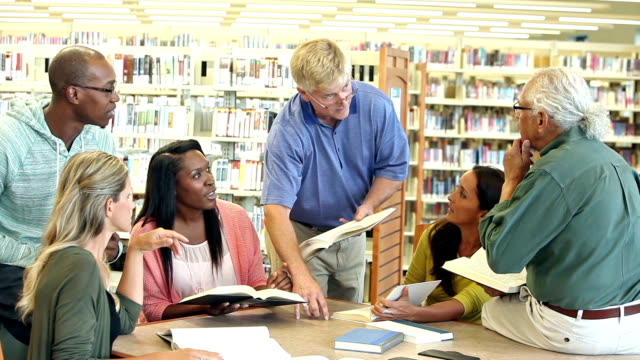 Group of adult students studying in library