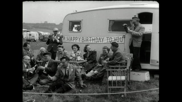 group of adults celebrate a birthday on a caravan site; 1950 - western script stock videos & royalty-free footage