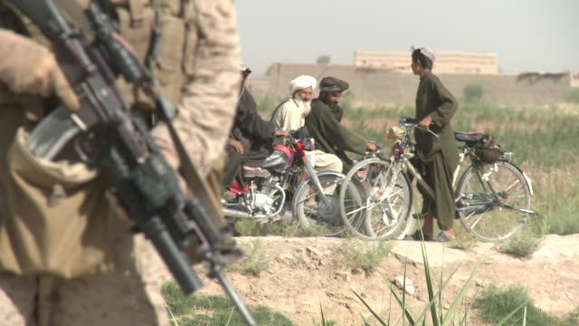 vidéos et rushes de a group of  afghan men break a meeting up as u.s. marines pass nearby. - afghanistan